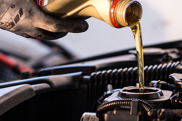 Mechanic fills the engine with engine oil