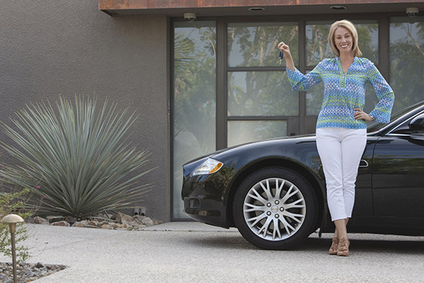 Woman standing in her driveway with the keys to her new car