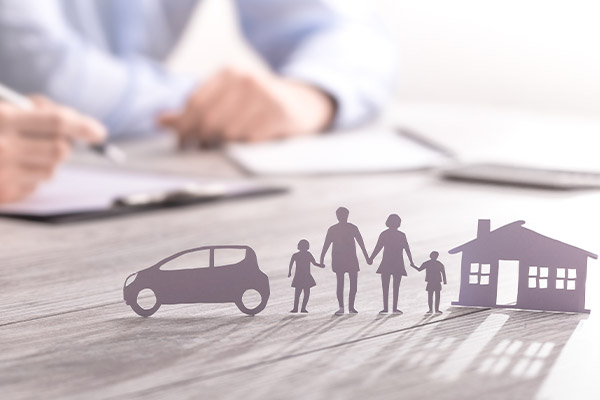 Paper cut outs of a family with a house and a car sitting on an office desk with business people doing paperwork in the background