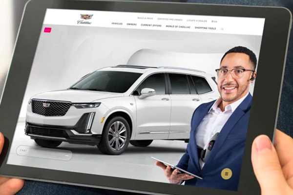 Cadillac sales person on a tablet showing a car in their showroom
