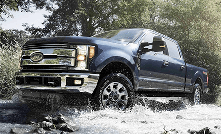 2018 Ford Super Duty LARIAT Crew Cab driving through off-road stream