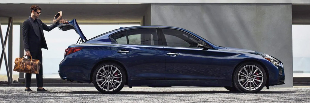 man opening the trunk of a luxurious grand blue 2021 INFINITI Q50, showcasing its side profile.