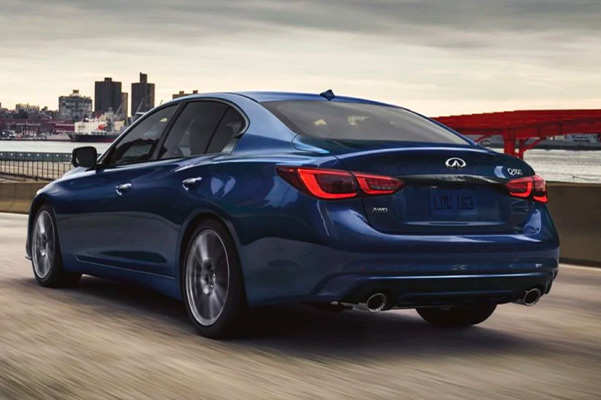 Rear profile of a grand blue 2021 INFINITI Q50 driving fast on the road.