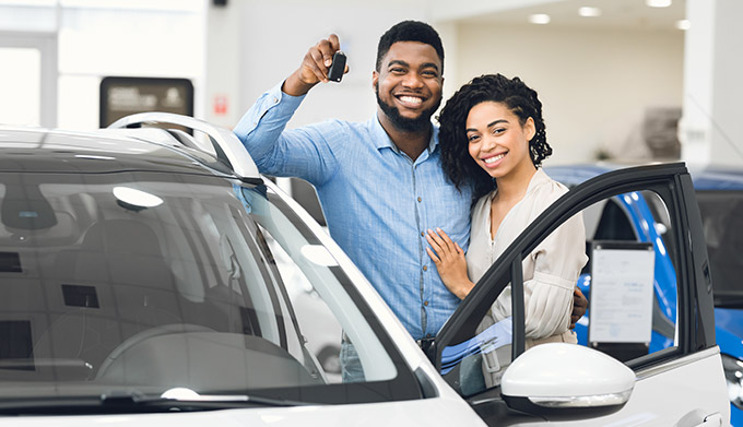 Couple holding keys to a new car
