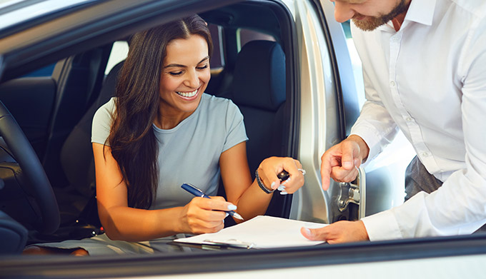 Woman signing papers at dealership